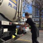 A hospitality worker gets water from a tanker in the Octagon. Photo: Chris Morris
