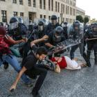 Protesters are pushed back by riot police during a demonstration following a not guilty verdict...