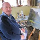 Alexandra artist Denis Kent works on a painting in his home studio. Kent, whose artworks have...