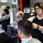 Bloke customer Harry Huang gets his hair cut by owner Keri O'Connor, without a drink in hand....
