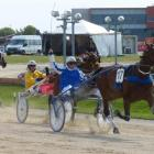 Co-trainer and driver Jonny Cox salutes behind Jaccka Justy in the Dominion Trot at Addington...