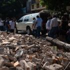 People walk by debris during a funeral ceremony held for a person that died in the earthquake in...