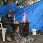 John Carvalho warms his hands at an open fire as wind and rain buffet his whitebait camp near...