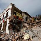 Soldiers remove the debris of a house destroyed in an earthquake that struck off the southern...
