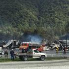 Fire crews mop up the twisted metal remains of an aircraft hangar, an engineering workshop and a...