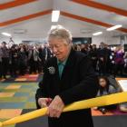 Years of effort ... Library lobbyist and former city councillor Anne Turvey cuts the ribbon to...