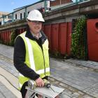 Oasis Greenery Systems  manager Darren Rice holds a component of a green wall being installed in...