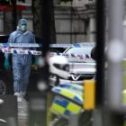A forensics officer walks near the Natural History Museum, after a car mounted the pavement, in...