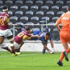 Otago winger Jona Nareki scores in the corner despite the efforts of Southland first five-eighth...