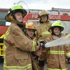 Charitable youngsters Taylor McLean, second from left, and her sister Kate try using a fire hose...