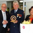 Volunteer firefighter Jim Shaw (centre), of Arrowtown, with partner Thalia Dunn, is honoured by...