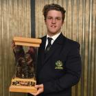 Otago second five eighth Tei Walden holds the David Latta Trophy after being presented with it at...