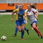Eleanor Isaac (centre) is on attack for Southern United as Auckland's Elizabeth Anton attempts to...