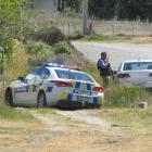 Police gather beside Lowburn Valley Rd, near Cromwell, as the search for an armed teenager...