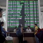 Passengers ask staff about their flights near the flight screen at Ngurah Rai airport. Photo:...