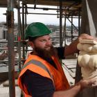 Stonemason Sam Dooley, of Oamaru, holds a crocket, one of the dozens of replacement Oamaru stone...