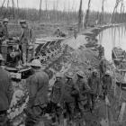 Gunners loading pontoon boats with shells brought in on a light railway. - Otago Witness, 7.11...