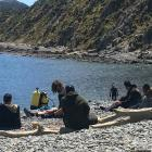 Friends and family take a break during the search for a missing 24-year-old New Plymouth diver at...