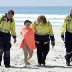 Brighton Fire and Emergency New Zealand volunteers help a woman to an ambulance after she was...