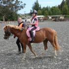 Volunteer Georgia Coleclough (15) leads Brooke Agnew (7) on Uli at the Riding for the Disabled...
