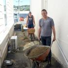 Property owner Phil Seaton (front) and Steve Green wheelbarrow loads of fill at Mr Seaton's...