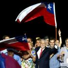 Pinera and his wife Cecilia wave flags after winning Chile's presidential election, in Santiago....