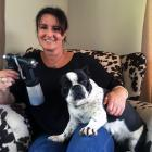 Primed Spray Tanning owner and operator Carmen Copland holds her spraygun and French bulldog...