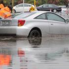 A car swamped by floodwaters in Carribean Dr is cleared from the road. Photo: NZ Herald