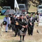 Piper  Alex Joyce, of Alexandra, leads in the group  to inter the ashes of Wing Commander Arthur ...