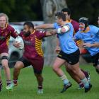 Alhambra Union wing Peni Qauqau - Dodds fends off University A halfback Dan Crowley during a...