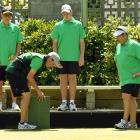 Caleb Hope (front left with mat) checks a measure from a bowl on the edge of the green to the...