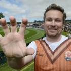 Craig Dougherty shows off the hand which held a $50,000 catch at the University Oval on Saturday....