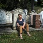 New Kaitangata resident Denise Dent sits in front of headstones at the local cemetery, including...