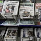 Newspapers are seen with headlines relating to the phone hacking scandal, near Westminster in...