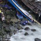 Rescue workers work at the scene after a bus crashed with a truck and careened off a cliff along...