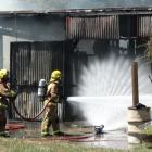 Firefighters dampen down a fire that took hold in the workshop of this Arthurs Point home...