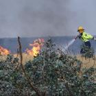 A volunteer firefighter goes up against the flames. Photos: Tracey Roxburgh