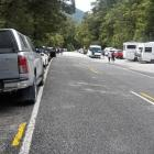 Cars and camper vans are parked beside State Highway 6 near Makarora while their occupants visit...