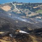 A lone firefighter stands on Mt Alpha looking down at the smouldering land. Photos: Sean Nugent...