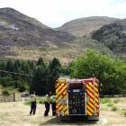 A Wanaka volunteer fire crew monitors a spot fire 300m up the eastern flank of Mt Alpha. PHOTO:...