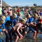 The starting gun sounds and  about 20 children sprint into the water at the start of the Little...