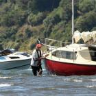Brent Young (left, in power boat) prepares to tow a stricken yacht off a mud-bed near the...