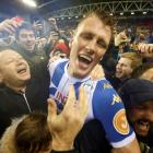 Wigan Athletic's Dan Burn celebrates with fans on the pitch after the match. Photo: Reuters