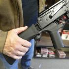 A bump stock device, (left) that fits on a semi-automatic rifle to increase the firing speed,...