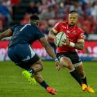 Lions first five-eighth Elton Jantjies is challenged by Bulls prop Lizo Gqoboka during their...