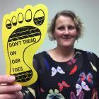 Saddle Hill Community Board deputy chairwoman Leanne Stenhouse holds a ''yellow feet'' card,...
