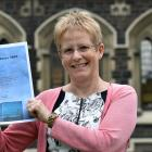 Prof Helen Nicholson holds a copy of the celebration schedule for the University of Otago's 150th...