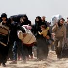People walk with their belongings as they flee the rebel-held town of Hammouriyeh, in the village...