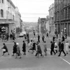 Pedestrians cross at the Princes St-Dowling St Barnes Dance in the late 1960s. Queens Gardens is...