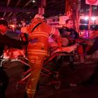 Paramedics and members of the FDNY perform CPR on a victim of a helicopter that crashed into the...